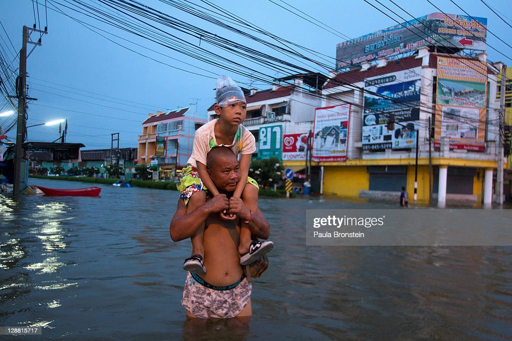A Thai man holds his daughter a he wades through the flooded streets October 10, 2011 in Ayutthaya, Thailand. Around 200 factories closed in the central Thai province of Ayutthaya because of flooding, which is posing a threat to Bangkok as well. Over 260 people have died in flood-related incidents since late July according to the Department of Disaster Prevention and Mitigation. Some areas of the country are experiencing the worst flooding in 50 years, mainly in the centre, north and northeast.