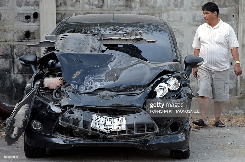 "A Thai man looks at cars damaged in road accidents over the New Year at a police station in Bangkok on January 3, 2013. A total of 365 people were killed and 3,329 injured in 3,176 road accidents throughout the country over the ""seven dangerous days"", running from December 27, 2012 to January 2, 2013."