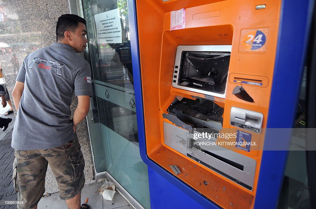 A Thai man looks at damage of Bangkok Bank branch following an army assault on an anti-government protest site in downtown Bangkok on May 20, 2010. Plumes of smoke hung overhead and gunfire crackled as Bangkok emerged from an curfew aimed at quelling mayhem unleashed by enraged anti-government protesters targeted in an army offensive.