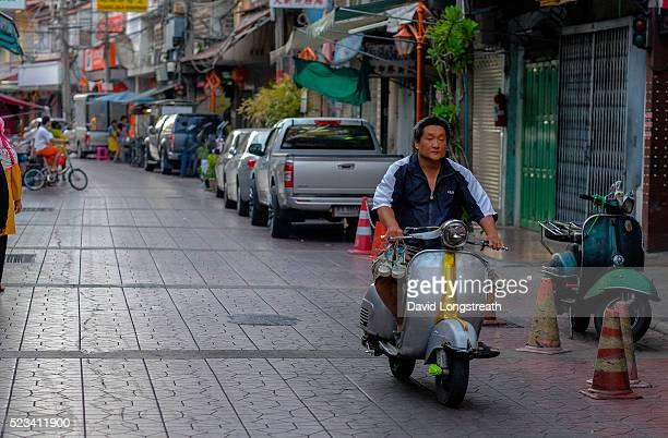 Thai man rides a vintage Vespa motorcycle in a back alleyway
