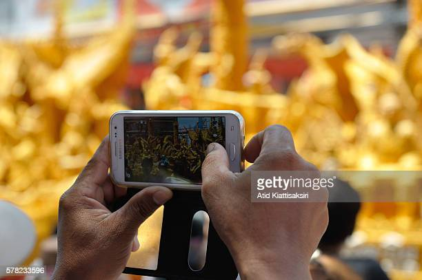 Thai man using his Samsung smartphone captures the candle parade during Candle festival in the downtown of Nakhonratchasima The Candle festival is...