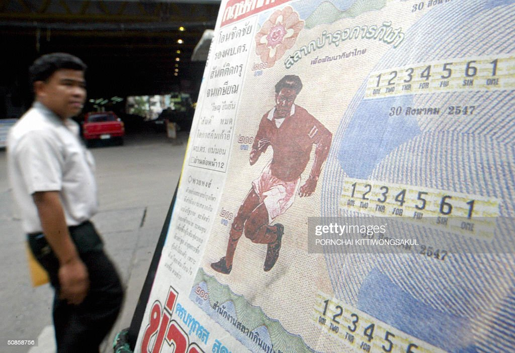 A Thai man (L) walks past a local newspaper showing the new lottery ticket in Bangkok, 20 May 2004. Thailand holds a public lottery to fund the purchase of a 30 percent stake in Premier League side Liverpool, as premier Thaksin Shinawatra said he was close to clinching the deal. AFP PHOTO/Pornchai KITTIWONGSAKUL