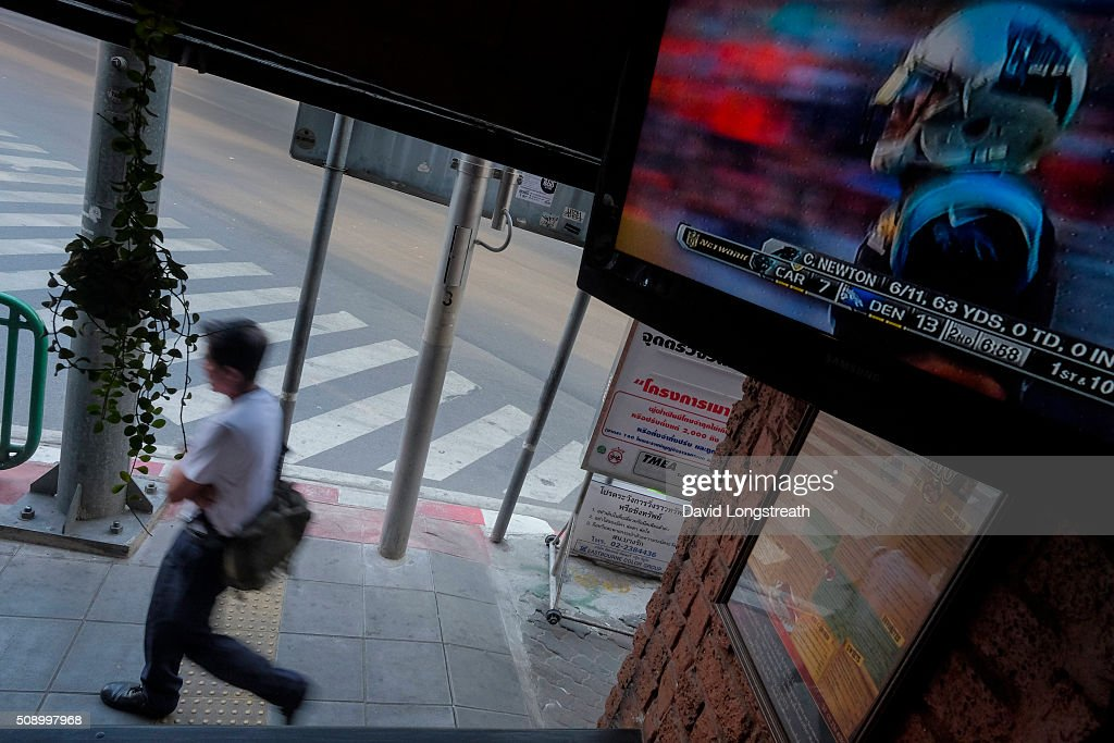 Thai man walks past a pub where ex-patriots and others gathered to watch Superbowl 50. The Denver Broncos defeated the Carolina Panthers 16-10 to win the football championship. The game was played in San Francisco and championship has been a part of American history since 1967.