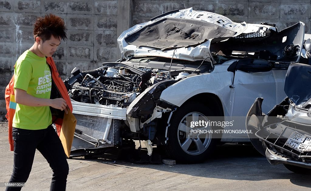 "A Thai man walks past cars damaged in road accidents over the New Year at a police station in Bangkok on January 3, 2013. A total of 365 people were killed and 3,329 injured in 3,176 road accidents throughout the country over the ""seven dangerous days"", running from December 27, 2012 to January 2, 2013."