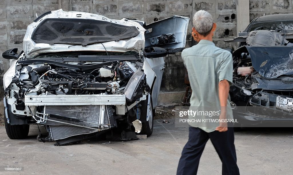 """A Thai man walks past cars damaged in road accidents over the New Year at a police station in Bangkok on January 3, 2013. A total of 365 people were killed and 3,329 injured in 3,176 road accidents throughout the country over the """"seven dangerous days"""", running from December 27, 2012 to January 2, 2013."""