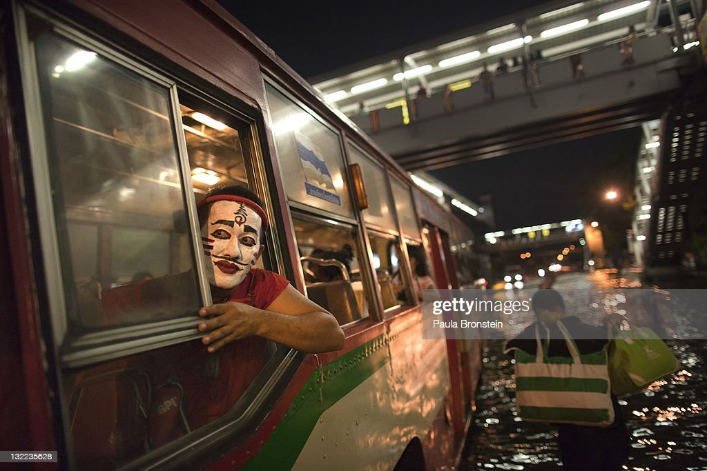 A Thai man with a painted clown face travels with other commuters as they head home on public transport through heavily flooded downtown streetsNovember 11, 2011 in Bangkok, Thailand. Over seven major industrial parks in Bangkok and thousands of factories have been closed in the central Thai province of Ayutthaya and Nonthaburi with millions of tons of rice damaged. Across the country, the flooding which is now in its third month, has affected 25 of Thailand's 64 provinces. Thailand is experiencing the worst flooding in over 50 years which has affected more than nine million people. Over 400 people have died in flood-related incidents since late July according to the Department of Disaster Prevention and Mitigation.