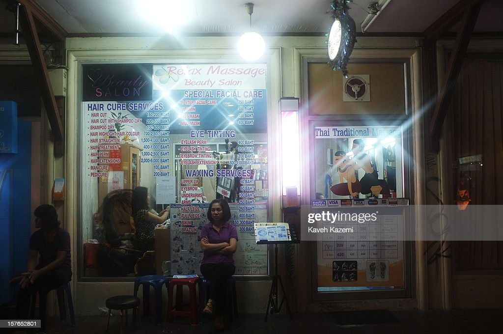 Thai masseuse sit outside a massage parlor waiting for customers on October 15, 2012 in Bangkok, Thailand.