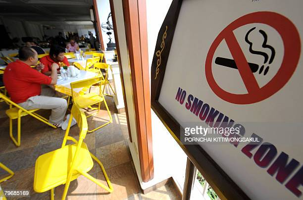 Thai men sit next to a nosmoking sign displayed at a restaurant in Pattaya on February 9 2008 This weekend is supposed to be the last chance for...