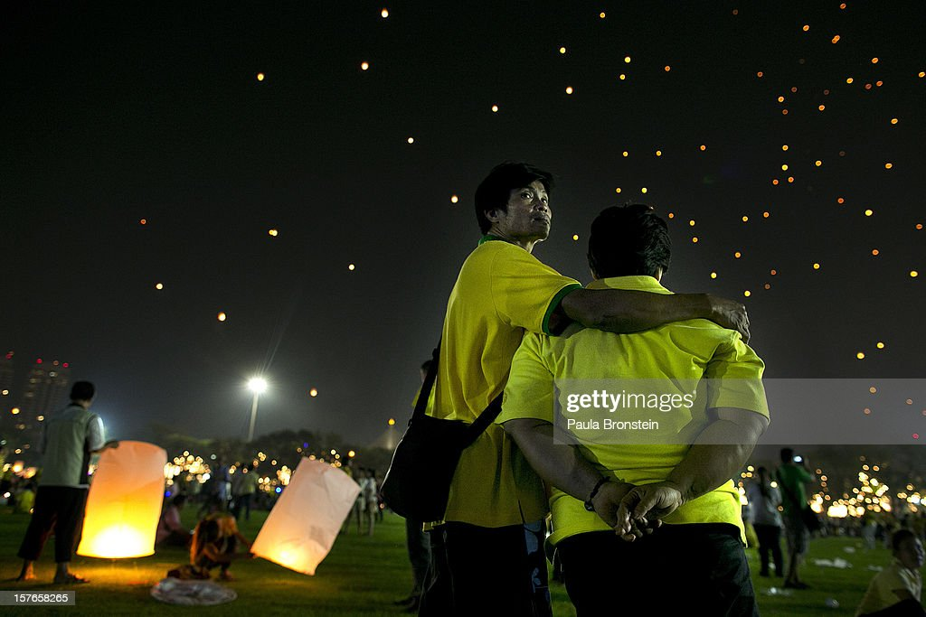 Thai men watch as lanterns float in the night sky during celebrations to pay respect to Thailand's King Bhumibol Adulyadej on his 85th birthday December 5, 2012 in Bangkok, Thailand. King Bhumibol took the throne in 1946, making him the world's longest reigning monarch and the world's longest serving head of state. Yellow represents Monday, the birthday of the King.