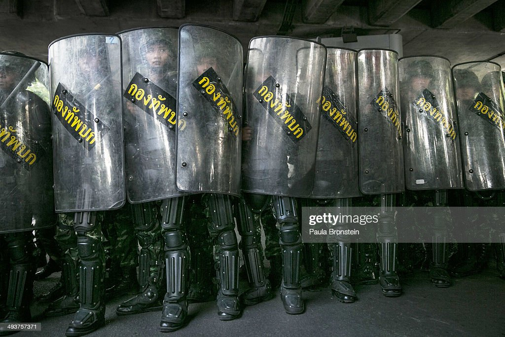 BANGKOK, THAILAND - MAY 25; Thai military stand behind their riot shields as protesters threaten them during an anti-coup protest on the third day of the military coup May 25, 2014 in Bangkok, Thailand. Thailand has seen many months of political unrest and violence which has claimed at least 28 lives. Thailand's coup leaders have detained former Prime Minister Yingluck Shinawatra, along with Cabinet members and other anti-government protest leaders. This is Thailand's twelfth coup in its history and there have been seven other attempted coups.
