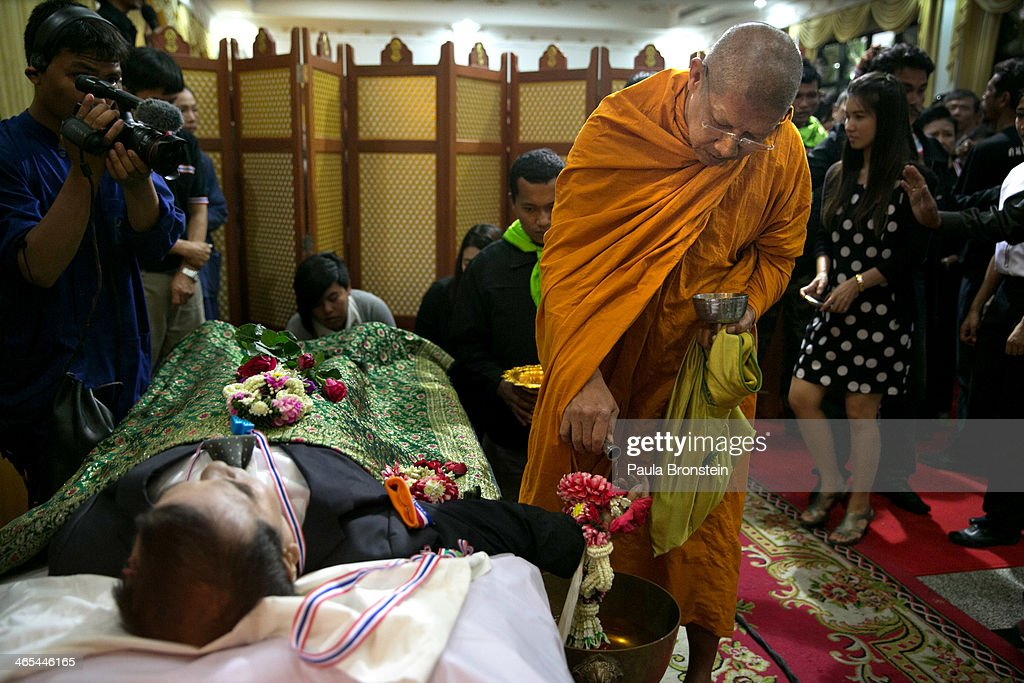 A Thai monk pays respects over the body of Sutin Tharatin, a core anti-government leader who was killed by gunmen yesterday in Bangkok on January 27, 2014 in Bangkok, Thailand. Nine others were also injured during election related violence as protesters blocked polling stations as advanced voting took place in the capital city. Bangkok Shutdown has been in effect for two weeks as the anti-government protesters continue to block major intersections. The Thai government imposed a 60-day state of emergency in Bangkok and the surrounding provinces in an attempt to cope with the on-going political turmoil but so far this decree has had no effect on the mass protests.