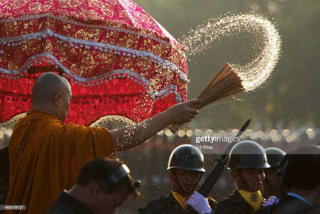 A Thai monk sprays water on parading soldiers as a blessing during a celebration of Thai Armed Forces Day at a military barracks on January 18, 2014 in Bangkok, Thailand. Thailand's Military, a powerful force in Thai society, has so far declined to become involved in Thailand's protracted political crisis