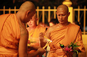 Thai monks holding candles during Asalha Puja Day celebration Thai culture or Asalha Puja Day celebrates the first teaching of Buddha Asalha is also...