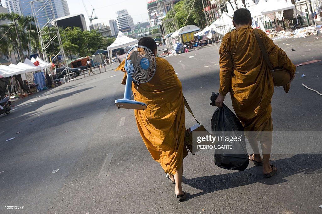 Thai monks leave the site of the Red shirt anti-government protesters camp in the financial center of Bangkok on May 20, 2010. Thai troops hunted for militant protesters who left parts of Bangkok in flames as the authorities extended a night curfew in the capital despite tentative signs of a return to normality.