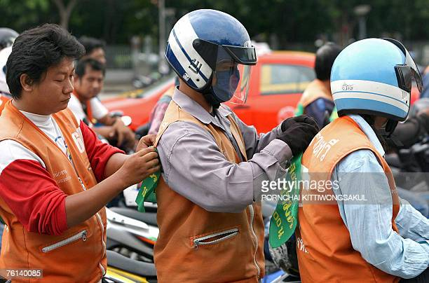 Thai motorcycle taxi drivers attach campaign banners to the back of their jackets during a campaign to urge people to vote in the upcoming Thai...