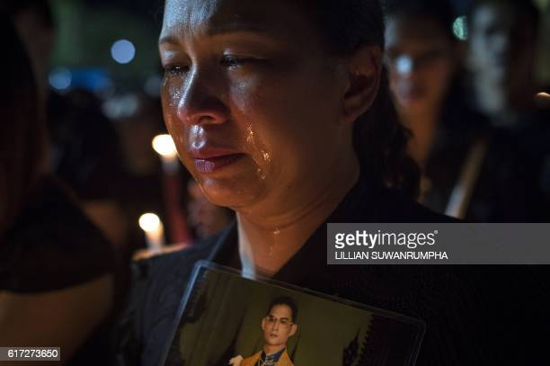 Thai mourner cries as others clad in black light candles for late Thai King Bhumibol Adulyadej at the Sanam Luang Park outside the Grand Palace in...