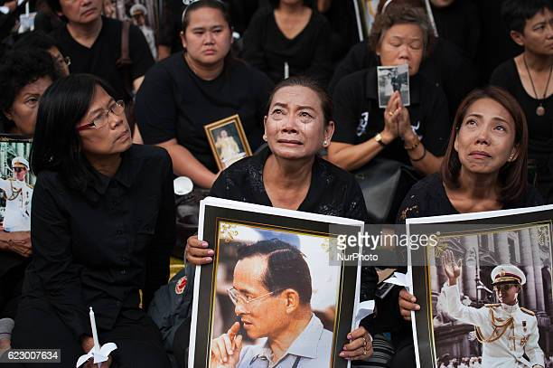 Thai mourners hold portraits of late Thai King Bhumibol Adulyadej at Siriraj Hospital in Bangkok Thailand on November 13 2016 Thousands of Thai...