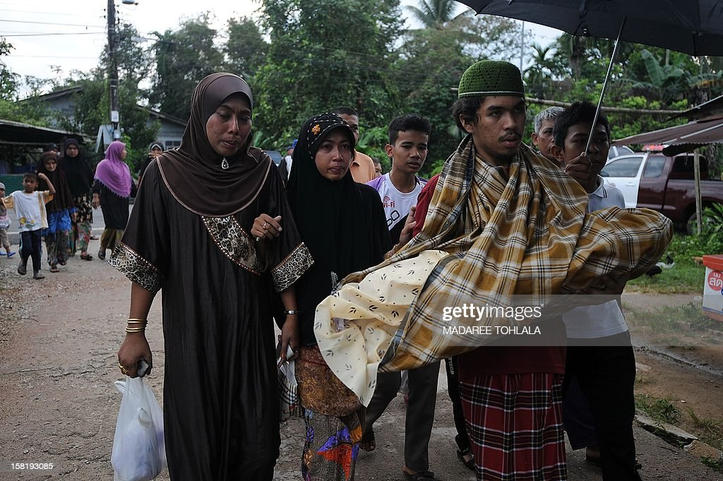 A Thai Muslim man carries the body of his 11-month-old daughter to her funeral after she was shot dead in an attack on a teashop by suspected separatist militants in Thailand's restive southern province of Narathiwat on December 11, 2012. Six people, including a one-year-old girl and two teachers, were gunned down in separate attacks on a teashop and school in Thailand's insurgency-plagued south on December 11, police said. AFP PHOTO / Madaree TOHLALA