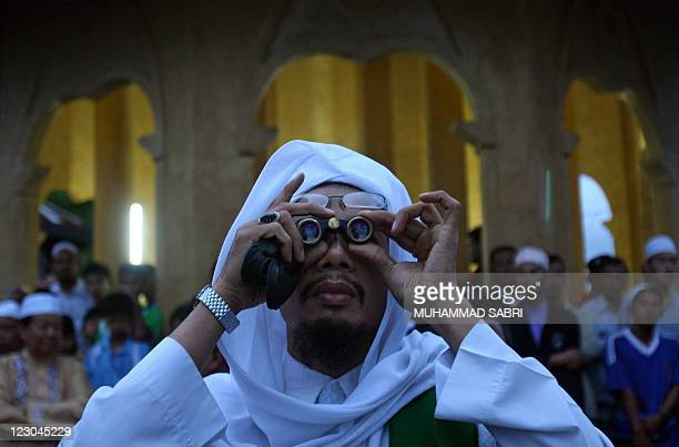 A Thai Muslim man uses binoculars to spot the moon on the eve of the end of the fasting month of Ramadan in Thailand's southern province of Yala on...