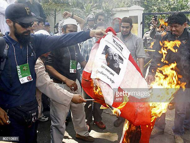 Thai Muslim protesters burn a Danish flag during a demonstration in front of the Danish embassy in Bangkok on March 12 2008 Hundreds of Thai Muslims...