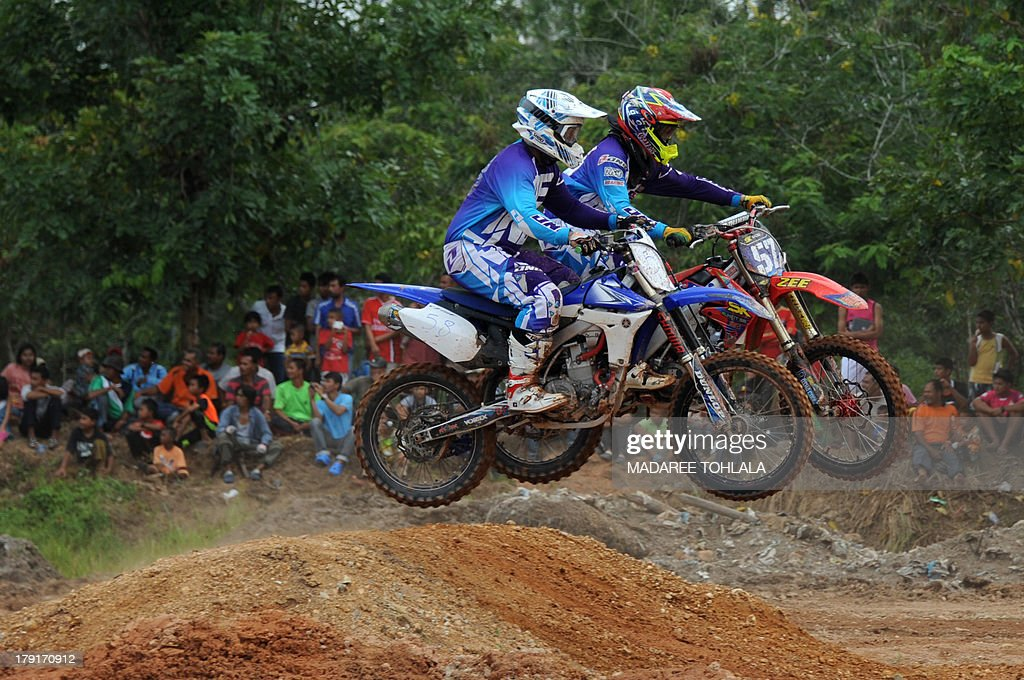 Thai muslim villagers attend a motorcross race between Thailand and Malaysia in Thailand's restive southern province of Narathiwat on September 01, 2013. Thailand and Malaysia motorcross races is one of the efforts to strengthen the relationship between the two countries. AFP PHOTO / MADAREE TOHLALA