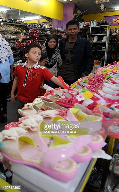 Thai Muslim villagers shop for shoes at a market in Thailand's southern province of Narathiwat on July 26 2014 ahead of the Eid alFitr festival The...