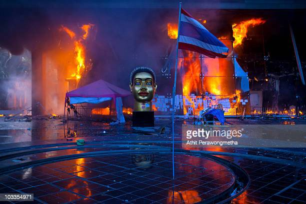Thai National Flag is seen inside the devastated red shirt camp as a fire burns at the Central World Shopping Mall on May 19 2010 in Bangkok Thailand...