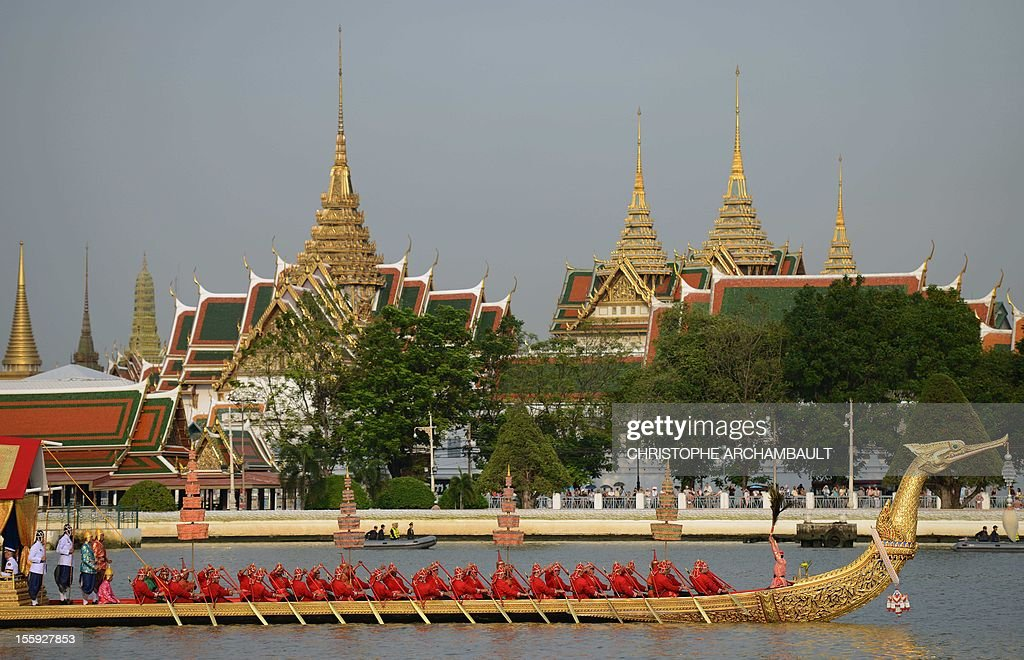 Thai Navy oarsmen row a barge in front of the Royal Palace during the Royal barge procession held on the Chao Phraya River in Bangkok on November 9, 2012. Over 2,000 rowers in 52 barges took part in the procession, held for the first time in five years and presided over by Crown Prince Maha Vajiralongkorn, and marking the upcoming 85th birthday of Thai King Bhumibol Adulayadej on December 5. AFP PHOTO / Christophe ARCHAMBAULT