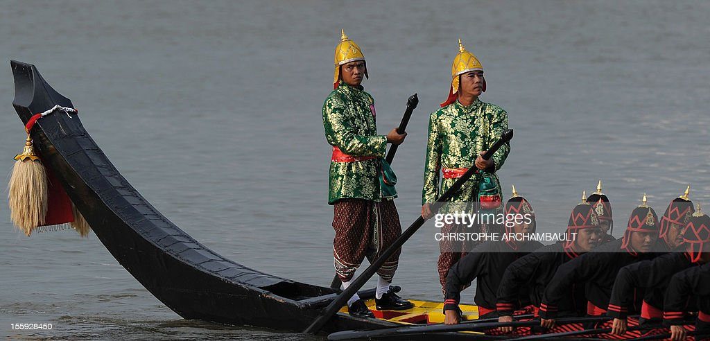 Thai Navy oarsmen row a barge in front of the Royal Palace during the Royal Barge Procession held on the Chao Phraya River in Bangkok on November 9, 2012. Over 2,000 rowers in 52 barges took part in the procession, held for the first time in five years and presided over by Crown Prince Maha Vajiralongkorn, and marking the upcoming 85th birthday of Thai King Bhumibol Adulayadej on December 5. AFP PHOTO/Christophe ARCHAMBAULT