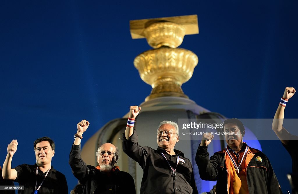 Thai opposition leaders Suthep Thaugsuban and former prime minister Abhisit Vejjajiva clinch their fists as they appear on stage during a rally at...