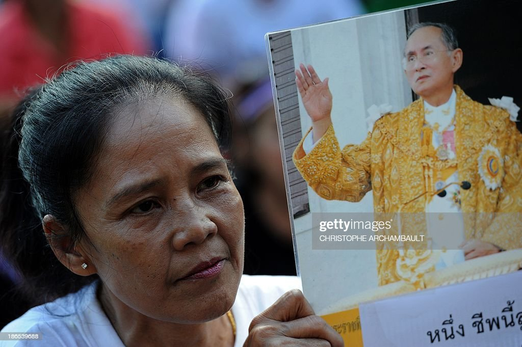 A Thai opposition protester holds a picture of king Bhumibol Adulyadej during a rally against an amnesty bill outside a railway station in Bangkok on November 1, 2013. Thailand's lower house of parliament passed a controversial political amnesty bill on November 1 that opponents fear will allow fugitive former premier Thaksin Shinawatra to return home and unleash fresh civil strife. AFP PHOTO/Christophe ARCHAMBAULT