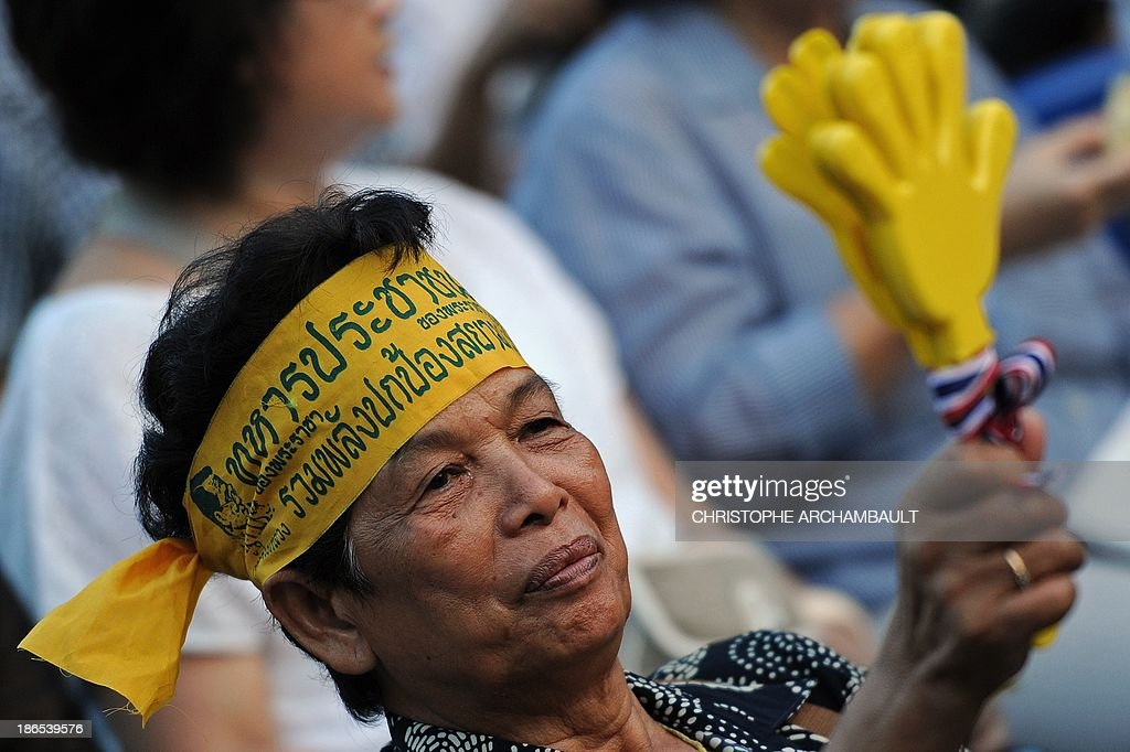A Thai opposition protester waves a clapper during a rally against an amnesty bill outside a railway station in Bangkok on November 1, 2013. Thailand's lower house of parliament passed a controversial political amnesty bill on November 1 that opponents fear will allow fugitive former premier Thaksin Shinawatra to return home and unleash fresh civil strife. AFP PHOTO/Christophe ARCHAMBAULT
