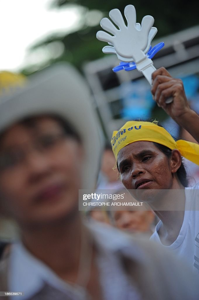 A Thai opposition protester waves clappers during a rally against an amnesty bill outside a railway station in Bangkok on November 1, 2013. Thailand's lower house of parliament passed a controversial political amnesty bill on November 1 that opponents fear will allow fugitive former premier Thaksin Shinawatra to return home and unleash fresh civil strife. AFP PHOTO/Christophe ARCHAMBAULT