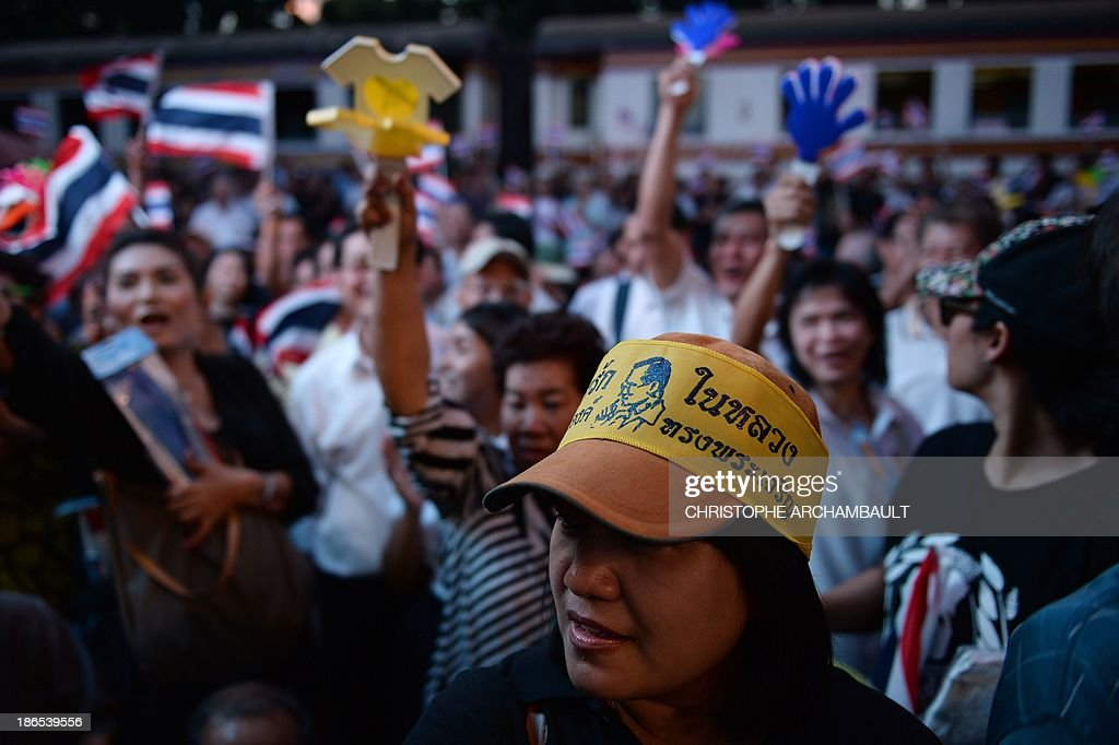 A Thai opposition protester wears a headband carrying a picture of revered king Bhumibol Adulyadej as others wave national flags and clappers during a rally against an amnesty bill outside a railway station in Bangkok on November 1, 2013. Thailand's lower house of parliament passed a controversial political amnesty bill on November 1 that opponents fear will allow fugitive former premier Thaksin Shinawatra to return home and unleash fresh civil strife. AFP PHOTO/Christophe ARCHAMBAULT
