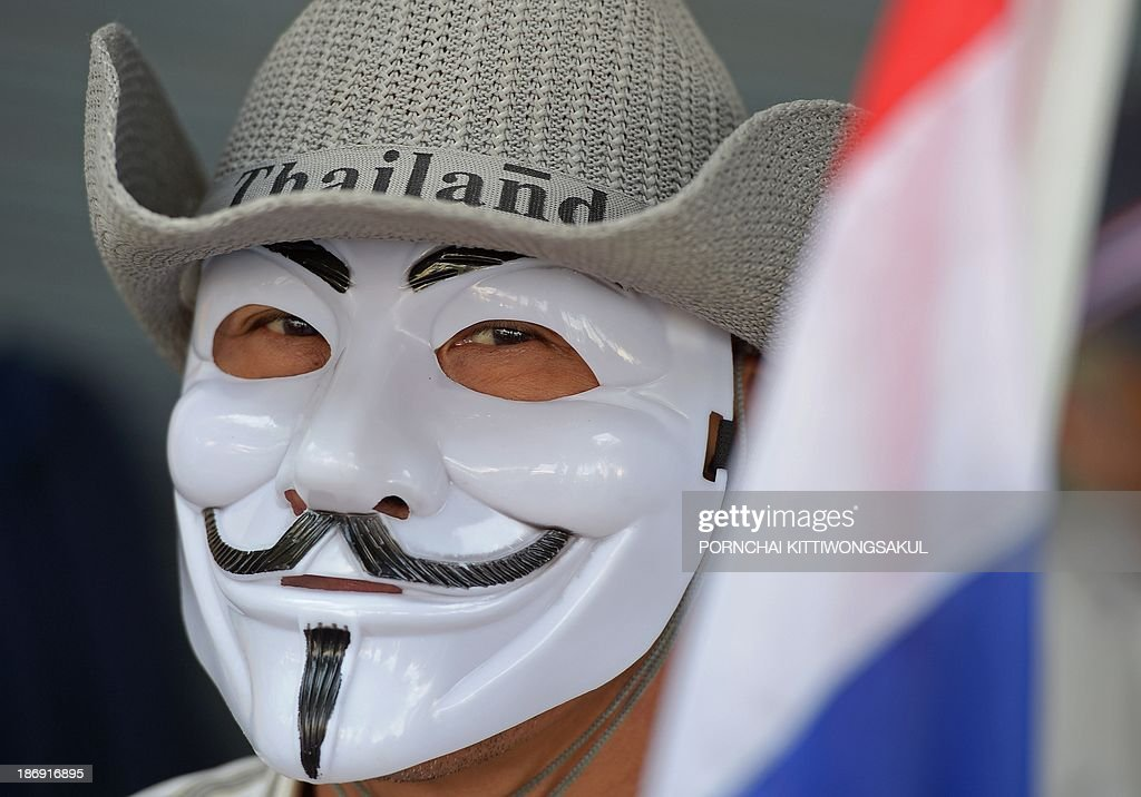 A Thai opposition protester wears a mask while carrying a national flag during a rally against an amnesty bill at Democray monument in Bangkok on November 5, 2013. Thai anti-government protesters gathered in Bangkok seeking to raise pressure on the Thai government over its controversial political amnesty bill.