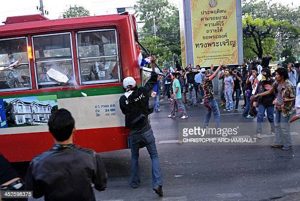 Thai opposition protesters attack a bus carrying progovernment Red Shirt supporters on their way to a rally at a stadium in Bangkok on November 30...