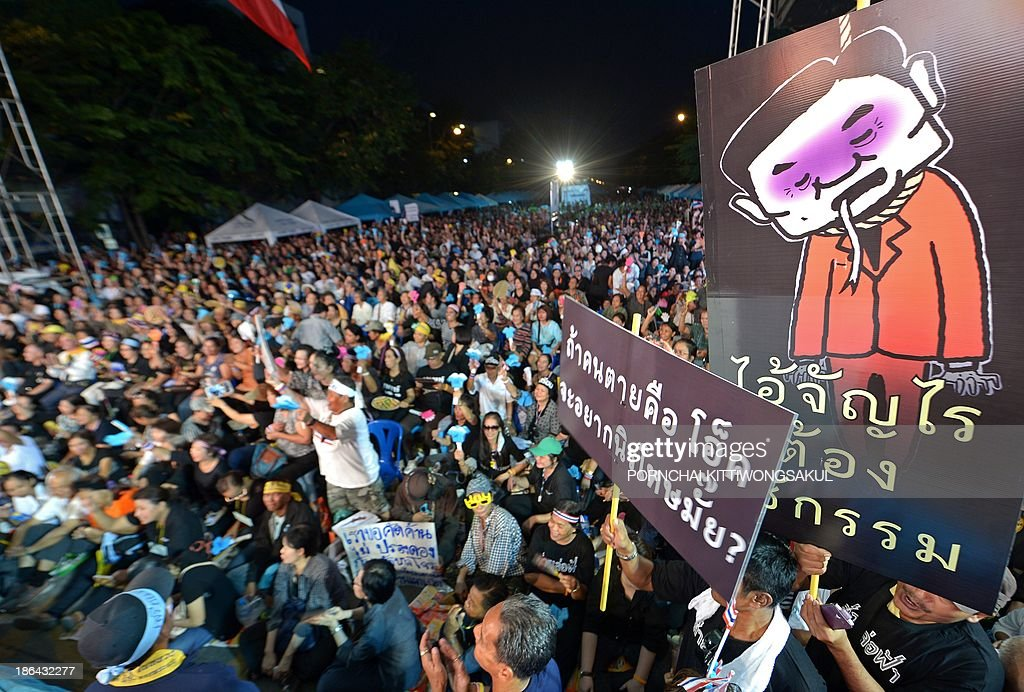 Thai opposition protesters hold protest placards as they rally against a planned amnesty at a railway station in Bangkok on October 31, 2013. Thailand braced for mass protests on October 31 as parliament debated a political amnesty that opponents fear will 'whitewash' the past killing of unarmed demonstrators and allow ousted premier Thaksin Shinawatra to return.
