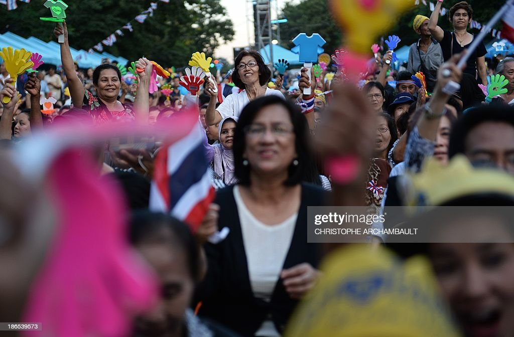 Thai opposition protesters wave clappers during a rally against an amnesty bill outside a railway station in Bangkok on November 1, 2013. Thailand's lower house of parliament passed a controversial political amnesty bill on November 1 that opponents fear will allow fugitive former premier Thaksin Shinawatra to return home and unleash fresh civil strife. AFP PHOTO/Christophe ARCHAMBAULT
