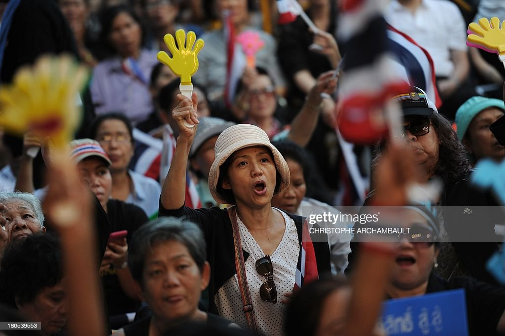 Thai opposition protesters wave national flags and clappers during a rally against an amnesty bill outside a railway station in Bangkok on November 1, 2013. Thailand's lower house of parliament passed a controversial political amnesty bill on November 1 that opponents fear will allow fugitive former premier Thaksin Shinawatra to return home and unleash fresh civil strife. AFP PHOTO/Christophe ARCHAMBAULT