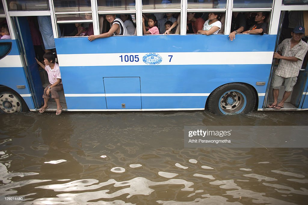 Thai passengers sit on the bus as floods continue to hit Pathum Thani province on October 14, 2011 in Pathum Thani, north of Bangkok,Thailand. Crews of public workers, soldiers and volunteers are evacuating residents from flooded areas north of Bangkok as efforts continue to protect the capital from increased rainfall and rising tides during the worst floods to hit the country for decades.