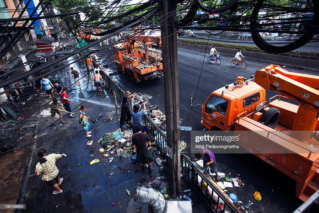 Thai people and workers clean an area of Rama IV after it was attacked during clashes between anti-government protester 'Red shirt' and Thai security forces at RamaIV street on May20, 2010 in Bangkok, Thailand. Thai Prime Minister Abhisit Vejjajiva says order has been restored to the capital Bangkok and throughout the country. A night-time curfew remains in place in Bangkok and 23 provinces are to prevent a resurgence of unrest. At least 44 people have been killed in clashes in which protesters clashed with military forces over a period of six consecutive days, resulting in the end of the blockade and the surrender of Red-shirt leaders.
