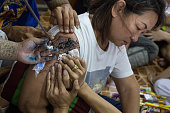 Thai people doing tattoo on the arm of a Thai pious Bouddhist woman in Nakhon Chai Si district Thailand about 50 km west of Bangkok on March 7 2015...