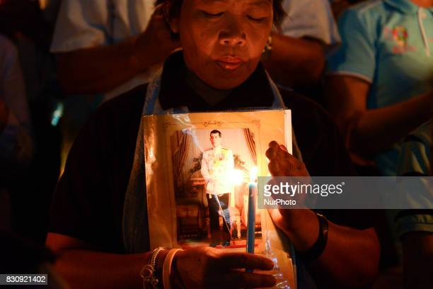 Thai people hold up pictures Thai King Maha Vajiralongkorn and lights candle his celebrate of Queens Sirikit birthday in Bangkok Thailand 12 August...
