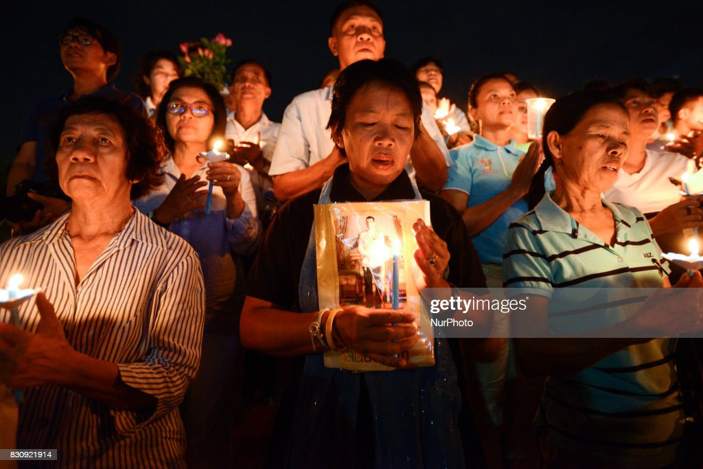 Thai people hold up pictures Thai King Maha Vajiralongkorn and lights candle his celebrate of Queens Sirikit birthday in Bangkok, Thailand, 12 August 2017.