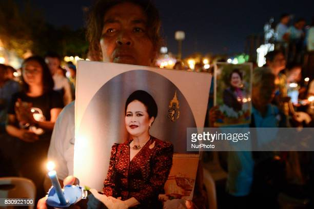 Thai people hold up pictures Thai Queens Sirikit and lights candle his celebrate of Queens Sirikit birthday in Bangkok Thailand 12 August 2017