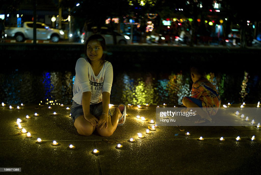 Thai people light lamps along the river on November 26, 2012 in Chiang Mai, Thailand. Chiang Mai is the largest and most culturally significant city in northern Thailand. It's a former capital of the Kingdom of Lanna (1296 - 1768) and was the tributary Kingdom of Chiang Mai from 1774 until 1939. In recent years, it has become an increasingly modern city and has been attracting over 5 million visitors each year, of which between 1.4 million and 2 million are foreign tourists.