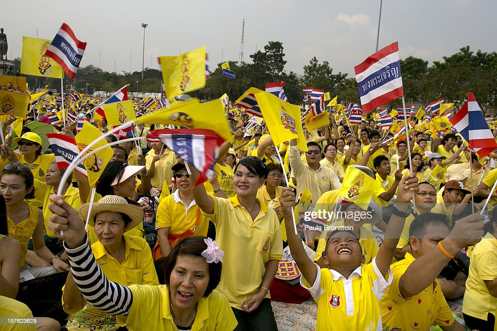 Thai people, wearing yellow, wave flags as tens of thousands come to pay respect to Thailand's King Bhumibol Adulyadej as he makes a rare public appearance on the occasion of his his 85th birthday, on December 5, 2012 in Bangkok, Thailand.King Bhumibol took the throne in 1946, making him the world's longest reigning monarch and the world's longest serving head of state. Yellow represents Monday, the birthday of the King.