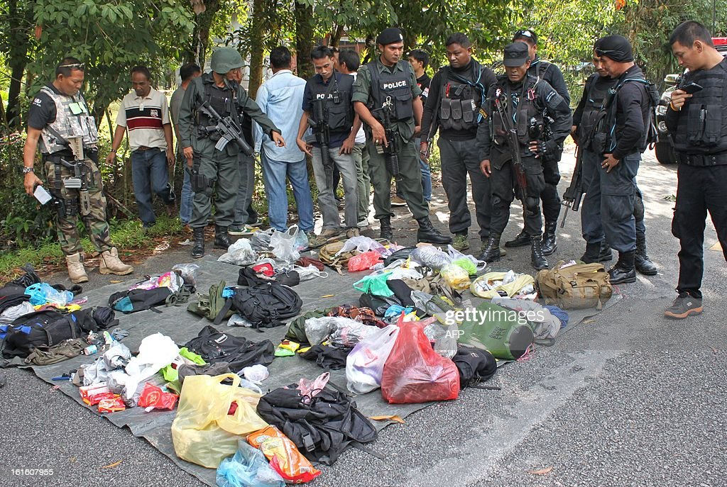 Thai police inspect belongings from dead suspected insurgents who were killed when they attacked a military base in Thailand's restive southern province of Narathiwat on February, 13, 2013. Scores of heavily armed gunmen stormed a military base in unrest-plagued southern Thailand, an army spokesman said, in a major assault that left at least 16 militants dead.