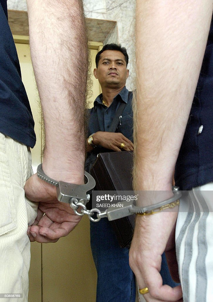 A Thai police officer (C) carries fake Italain passport and other proofs in a briefcase while taking handcuffed foreigners arrested in a raid in Bangkok, 20 May 2004. Two Europeans and a South African have been arrested in the Thai capital for allegedly forging hundreds of Italian passports and visa seals they planned to sell in Europe. AFP PHOTO/ Saeed KHAN