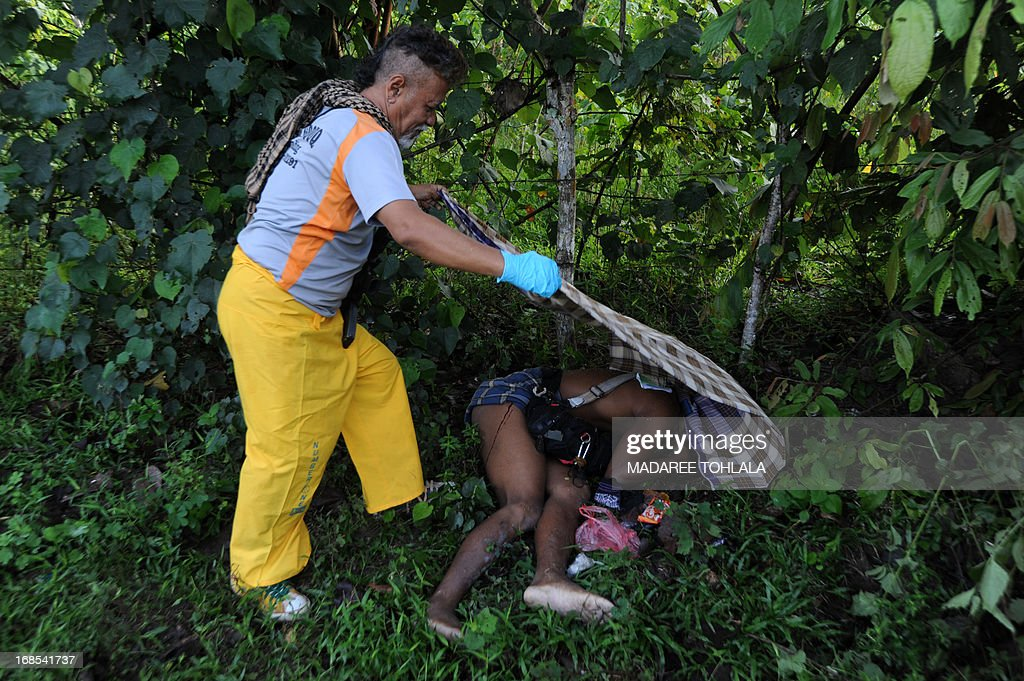 A Thai police officer in plain clothes cover the body of a suspected separatist militant who was shot dead during a clash with army rangers in the Rueso district of Thailand's restive southern province of Narathiwat on May 11, 2013. More than 5,500 people have been killed in Thailand's Muslim-majority south since 2004, with shadowy insurgent groups blamed for near-daily bombings and shootings. AFP PHOTO/ Madaree Tohlala